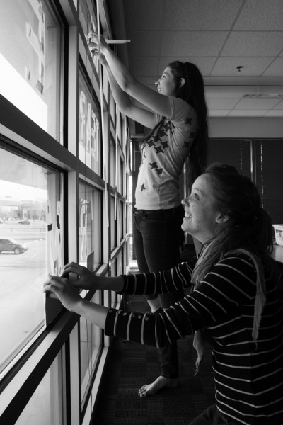 Arianna Sullivan (crouching) and Chelsea Alden (standing) prepare the final Snow Poem for painting with stencils.