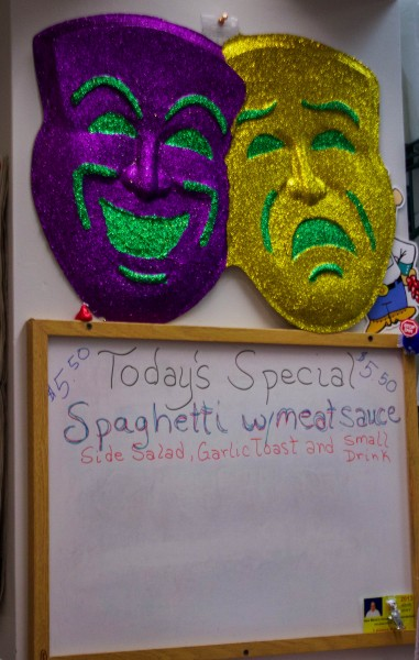 Fun Mardi Gras decorations adorn the wall above the day's menu.