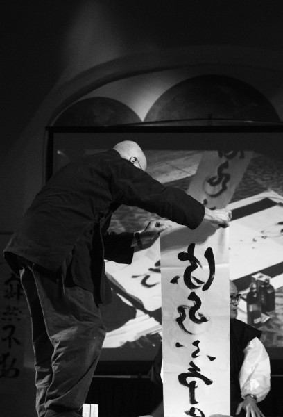 A member of the Tahoma Monastery holds up a zazen phrase for the audience to see.