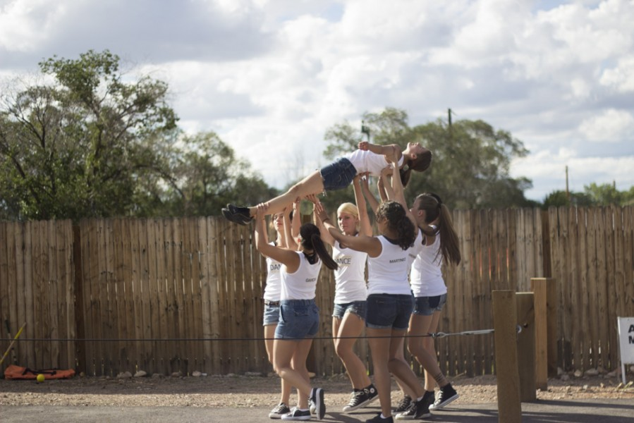 The dancers lift Mikyla Hutwohl overhead as they travel to the other side of the train tracks. Photo by Amanda Tyler