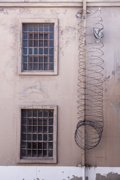 Concertina (razor) wire secures climbable lengths of pipe.