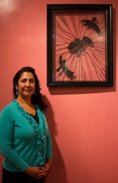 Rangel poses in front of a piece titled 'Beauty and the Beast.' Photo by Shayla Blatchford