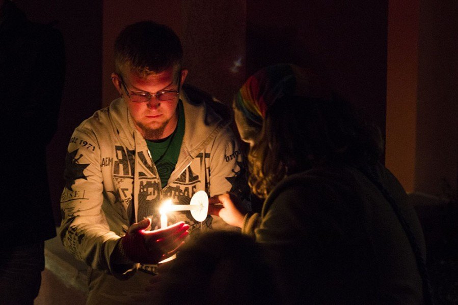 Cutlar Shell helps Cailin Kosman light her candle for the minute of silence. Photo by: Bego Aznar