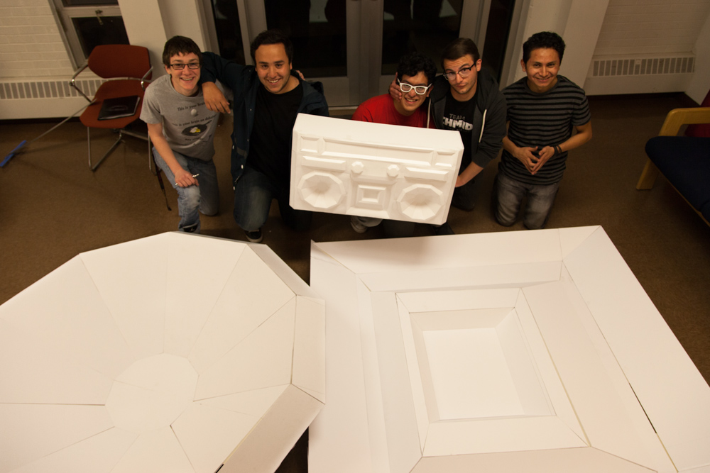 Abe Schor, Aldo Vidrio, Caleb Ortega, Brandon Schmidt and Arnold Mateos (left to right) hold up a small scale model of their boombox behind the beginning stages of the larger-than-life piece.
