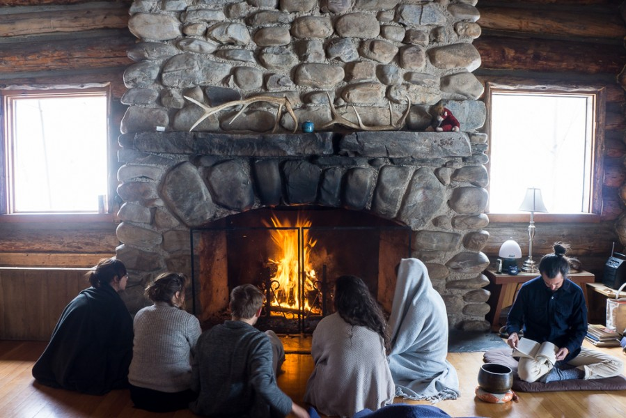 Students get cozy by the fire before morning practice. Photo by Luke Montavon