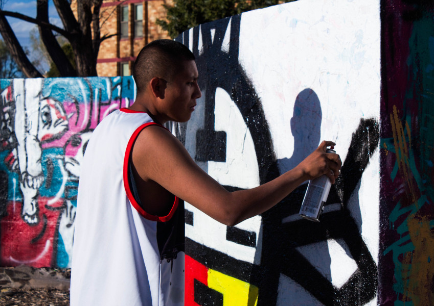 Young graffiti artist Edward Valdez spends the day doing his art. Photo by Charlotte Martinez