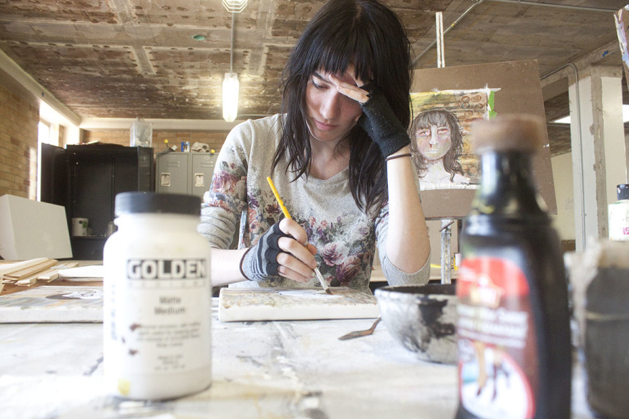 Stephanie Thompson paints in Alexis Hall. Photo by Andrew Koss