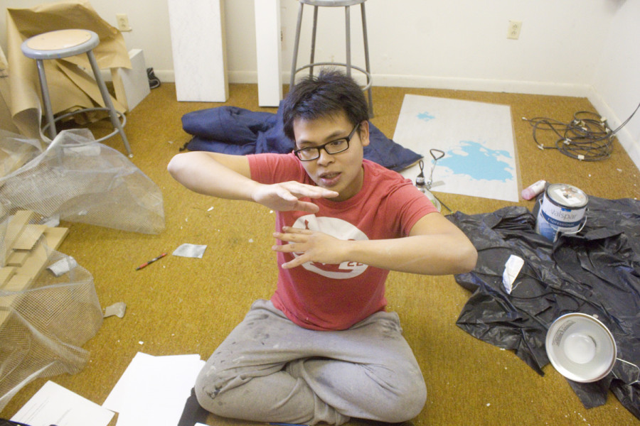 Junior Studio Arts major Phat Le explains his artistic process amid the clutter of his studio in the barracks. Photo by Andrew Koss