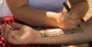 Melinda Freudenberger writes a quote from her favorite book on Andrew Koss' arm.