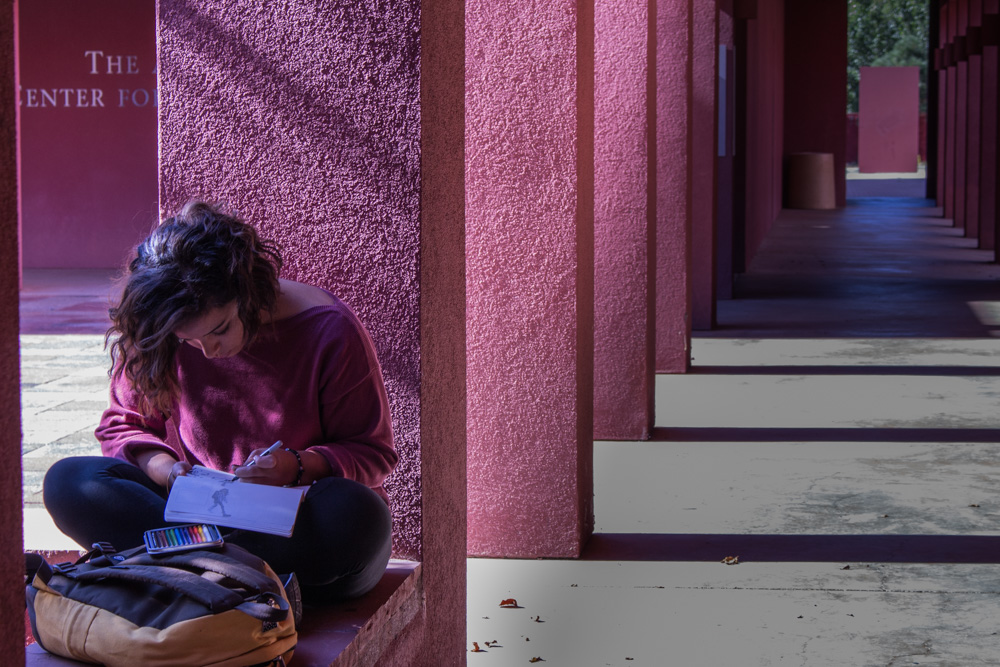 Ronnie Garcia, a junior digital arts major, sits in the Marion Center courtyard while she draws character sketches.