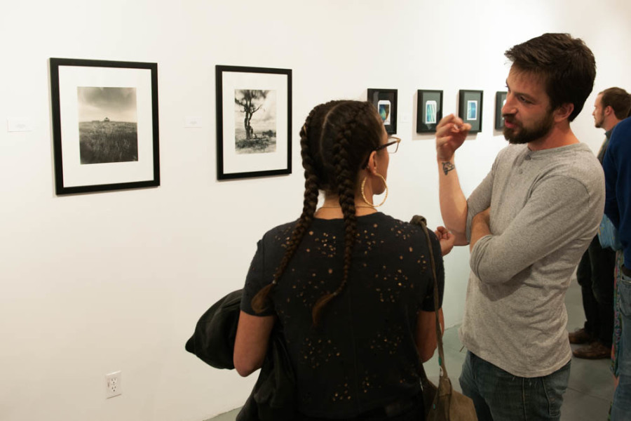 Andrew Coleman discusses his work with a fellow member of the Stangers Collective. Photo By Forrest Soper.