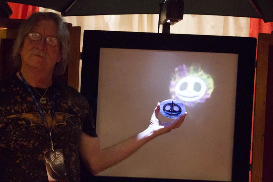 Richard Elvis displays how light affects the ornamental glass pieces he sells. Photo by Christy Marshall
