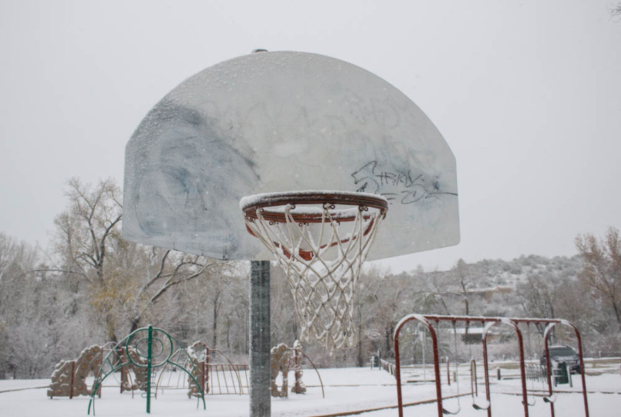 A frozen basketball hoop at an empty park. Photo by Kyleigh Carter.