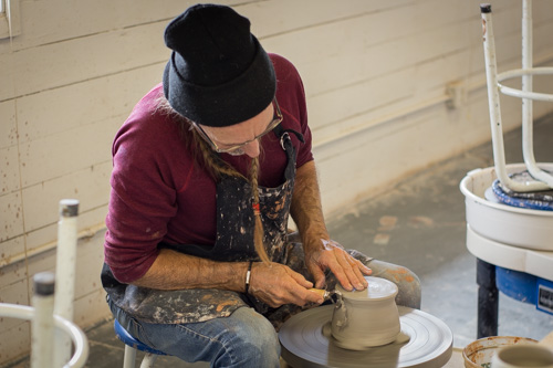Mike Sutton focused while working on the pottery wheel. Photo by Jason Stilgebouer