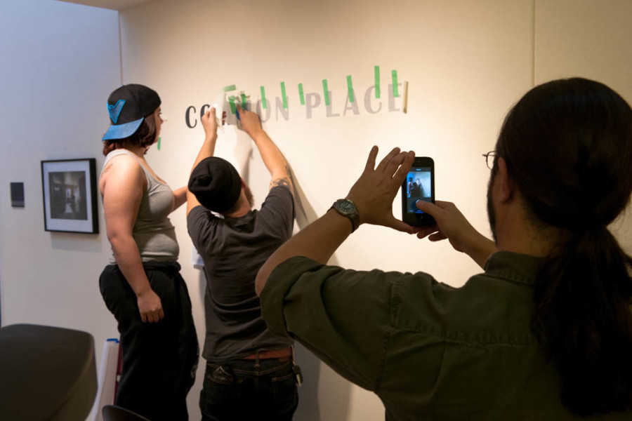 BFA students Samantha Podio and Brad Trone apply the vinyl lettering to their exhibition. Photo by Forrest Soper.