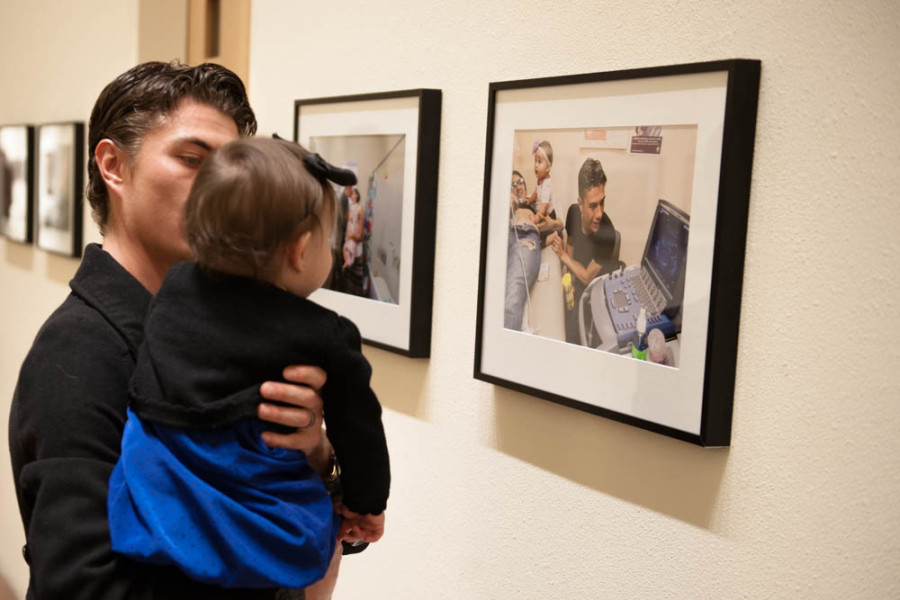 Ramon Sena and his daughter, the primary subjects of Podio's thesis, view photographs of themselves at the Marion Center. Photo by Forrest Soper.