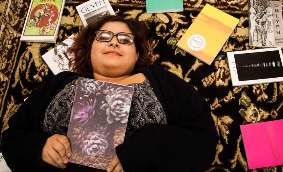 Amaya Hoke lies among past issues of Glyph. Photo by Christy marshall