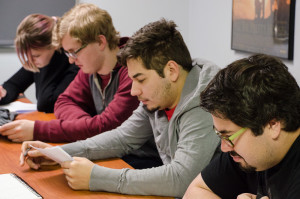 Students look over Marina Woollvey's screenplay for an in class reading. Photo by Rebeca Gonzalez