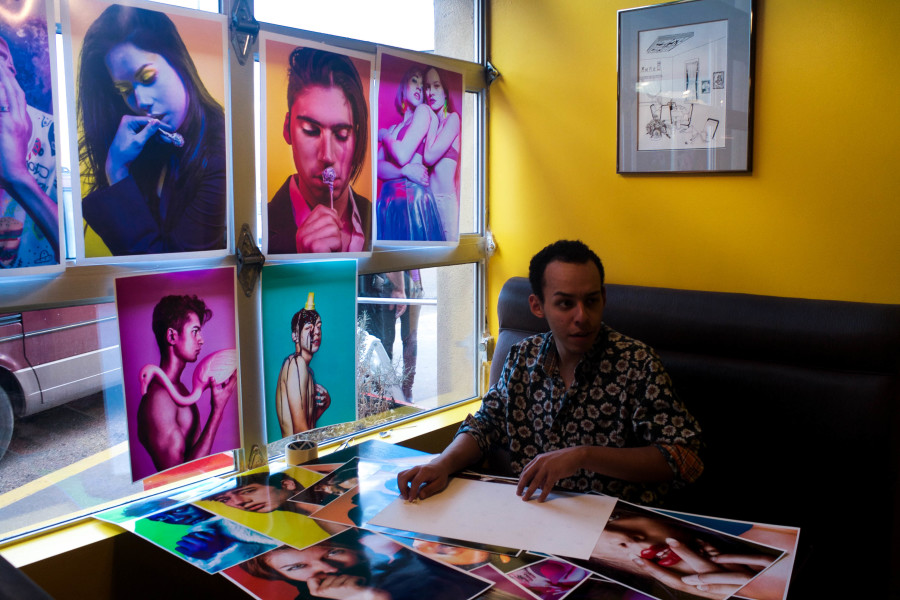 Photography major Marco Rivera organizing his prints for critique. Photo by Whitney Wernick.