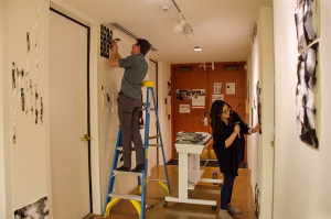 Jennifer Carrillo helps Craig Duncan hang his show for the EXIT Gallery. Photo by Rebeca Gonzalez