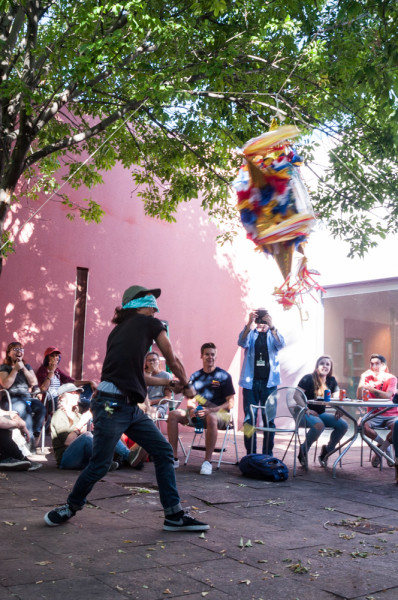 Freshman Photographer Richard Sweeting is practicing his swing on the pinata during the department barbecue. Photo by Sasha Hill