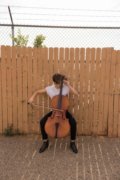 Lara White practices their cello harmonics publicly. Photo by Kaitlyn Sims.