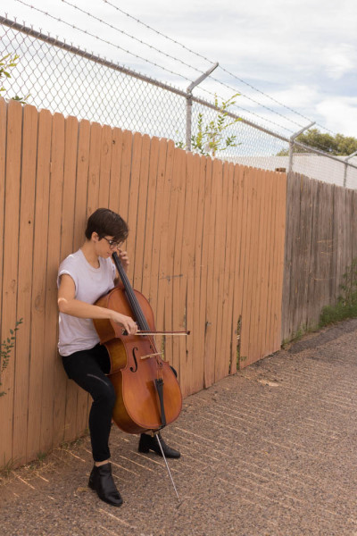 Lara White plays their cello in public to get some fresh air. Photo by Kaitlyn Sims.
