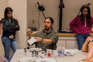 Technical faculty and Professor Chris Nail demonstrates the differences in inks used for spotting prints on dark room prints. Photo by Yoana Medrano.