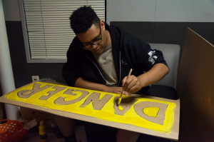 Digital Arts Sophomore Lorenzo Diaz decorating. Photo by Sasha Hill