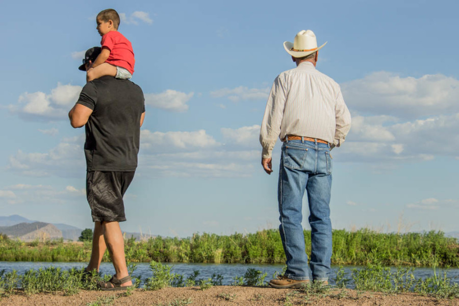 Traditionally dressed father looks out over his land while his son and grandchild continue to change and grow with time. Photo by Yoana Medrano.