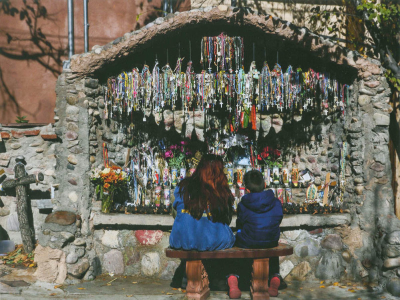 Two visitors sitting in front of a rosary decorated shrine in the El Santuario de Chimayo in Chimayo, NM. Photo by Eduardo Rocha.