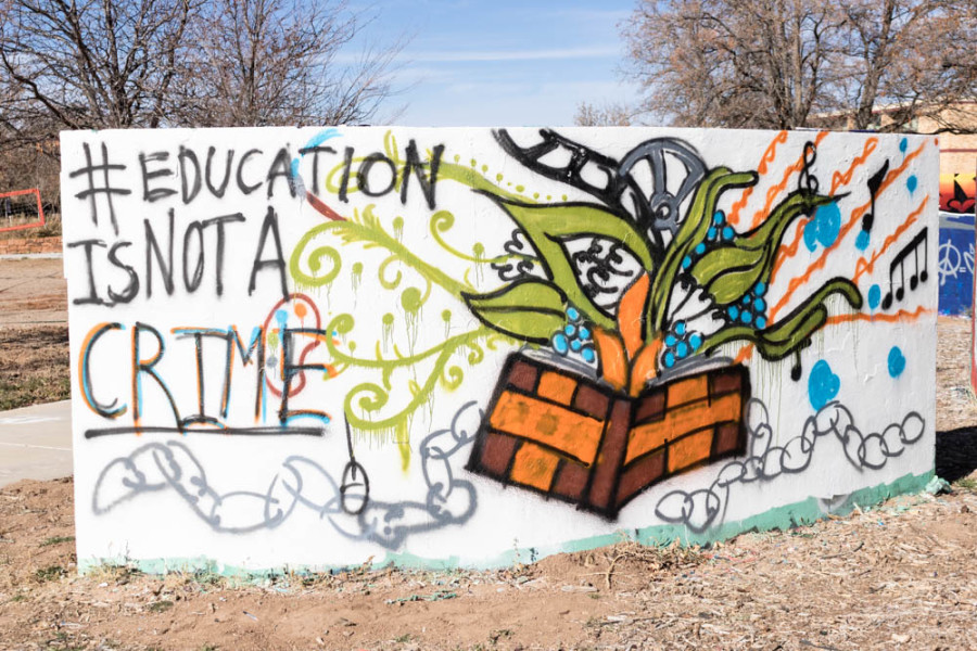 Student presents #EducationIsNotACrime mural on graffiti walls. Photo by Kaitlyn Sims.
