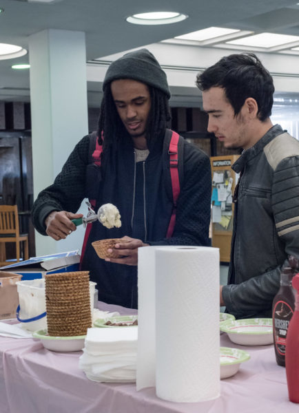 Senior Creative Music major Shar Clay scoops his vanilla ice cream into his waffle bowl. Photo by Sasha Hill