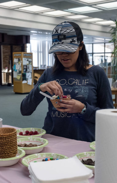 Sophomore Film major Jasmine Lee accessorizes her sundae with raspberries. Photo by Sasha Hill