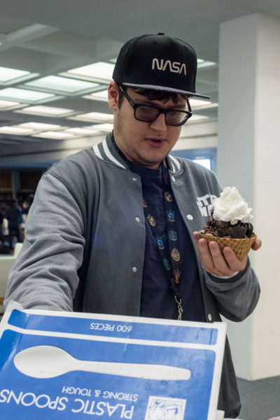 Sophomore Film major Jose Couvillion tops his sundae with whip cream. Photo by Sasha Hill