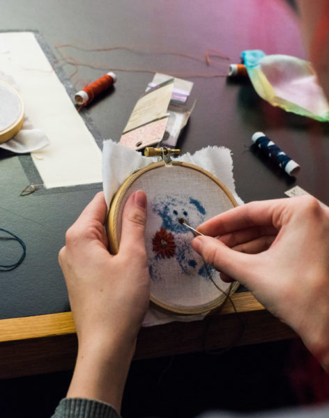 Christina Marshall delicately sews her cyanotype teddy. Photo by Sasha Hill