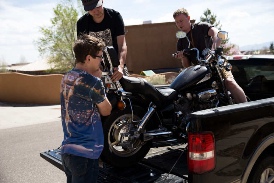 Aiden Willink and Derek Conkins help Ambrose Taylor lift his motorcycle into the Back of a truck to take back to campus. Photo by Jason Stilgebouer