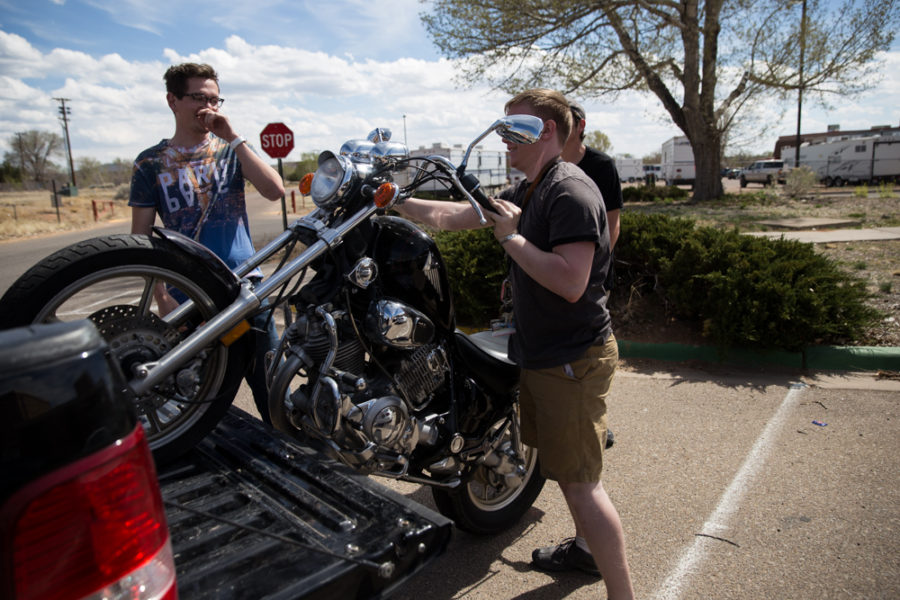 Aiden Willink and Derek Conkins help Ambrose Taylor unload his motorcycle out of a truck onto campus. Photo by Jason Stilgebouer