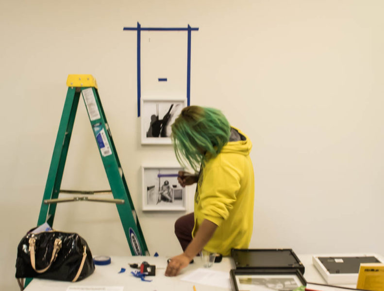 Hawie Veniegas precisely hangs his photos on the Fogelson Library wall. Photo by Lexi Malone