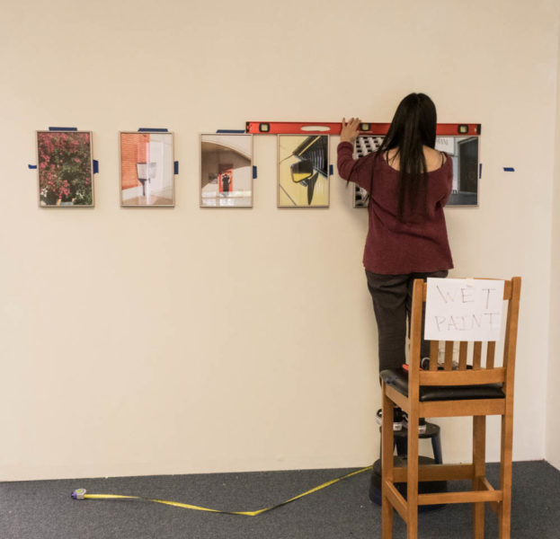 Jenn Carrillo makes sure her prints are leveled before she finishes hanging. Photo by Lexi Malone