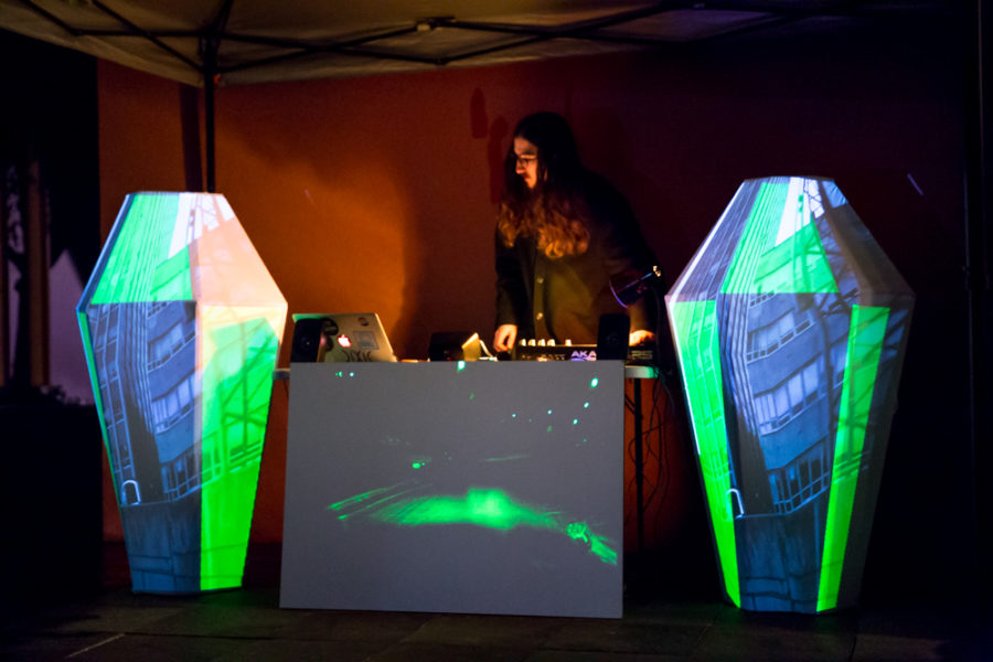 A Dj mixes music next Video mapping display at outdoor vision festival. Photo by Jason Stilgebouer