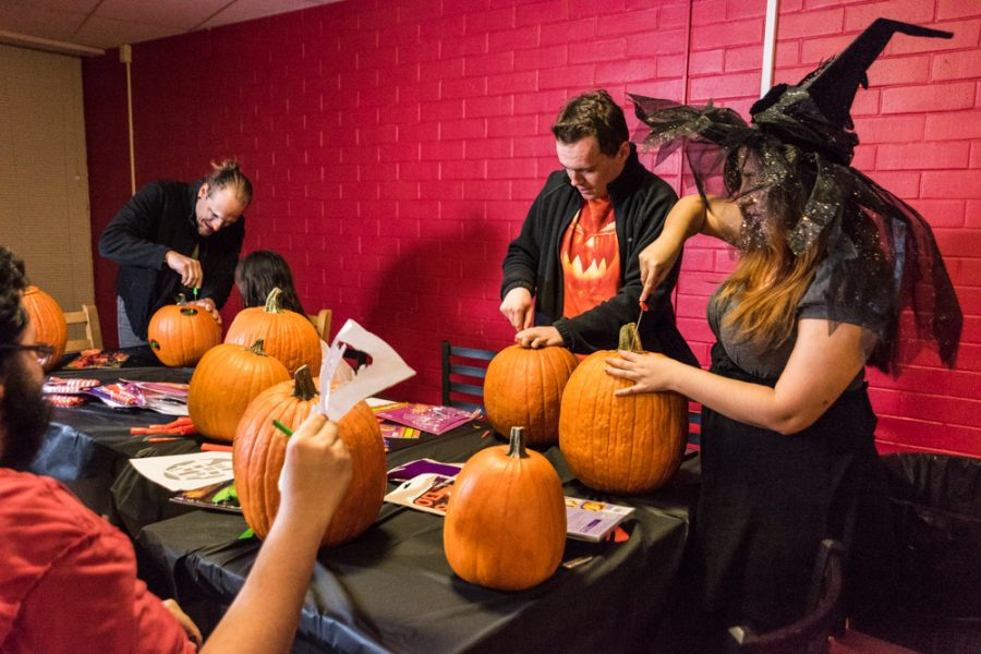 Students gather around the carving table as they begin to open up pumpkins. Photo by Sasha HIll