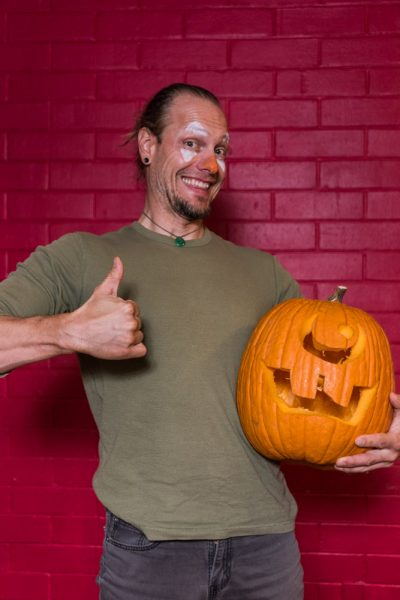 Raymond Davis enthusiastically poses with his carved pumpkin. Photo by Sasha HIll