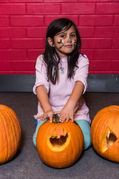 Alethia Hill sits with her carved pumpkin. Photo by Sasha Hill