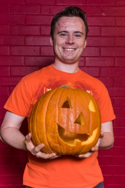 Jack Getschman happily displays his carved pumpkin. Photo by Sasha Hill