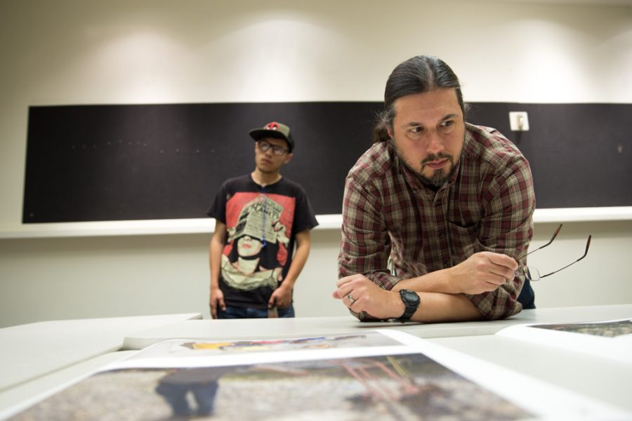 Photography teacher Chris Nail reviews Matthew Anderson's thesis in detail during the Santa Fe University of Art and Design Photography Department salon. Photo by Jason Stilgebouer