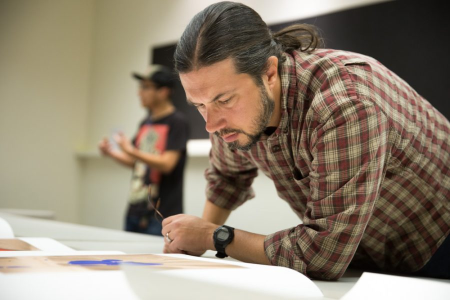 Photography teacher Chris Nail gets a closer look at Matthew Anderson's thesis in detail during the Santa Fe University of Art and Design Photography Department salon. Photo by Jason Stilgebouer