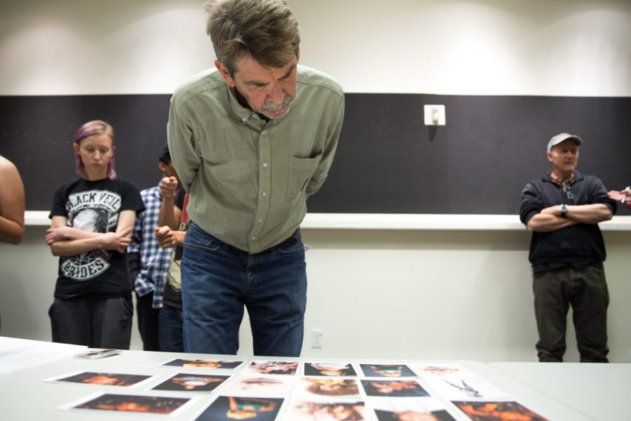 Faculty Tony O'Brien reviews Whitney Erin Wernick's work in detail during the Santa Fe University of Art and Design Photography Department salon. Photo by Jason Stilgebouer