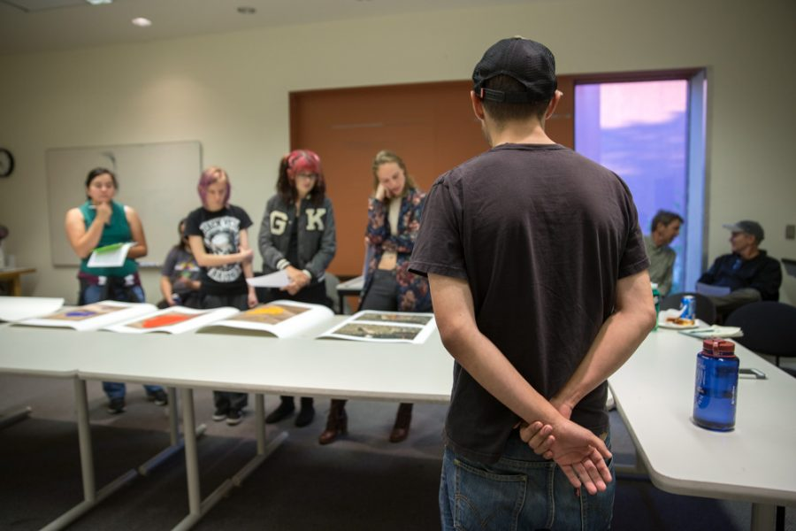 Matthew Anderson stands patiently as photography students review his work at the Santa Fe University of Art and Design Photography Department salon. Photo by Jason Stilgebouer