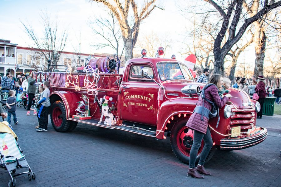 Parents pose with their kids at the vintage, decorated fire truck. Photo by Chris Dorantes